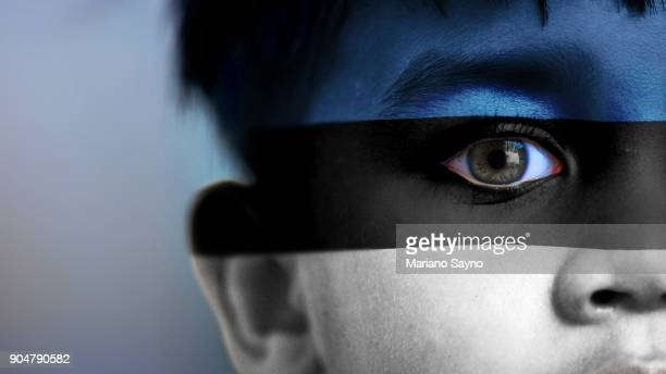 Boy's face, looking at camera, cropped view with digitally placed Estonia flag on his face.