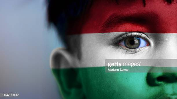 Boy's face, looking at camera, cropped view with digitally placed Hungary flag on his face.