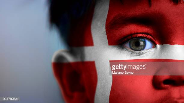 Boy's face, looking at camera, cropped view with digitally placed Denmark flag on his face.