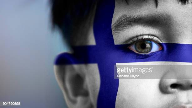 Boy's face, looking at camera, cropped view with digitally placed FInland flag on his face.