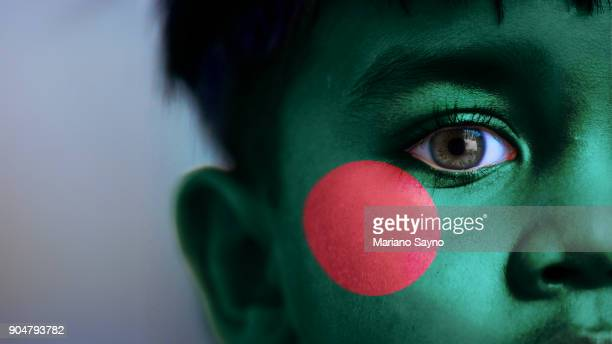 Boy's face, looking at camera, cropped view with digitally placed Bangladesh flag on his face.