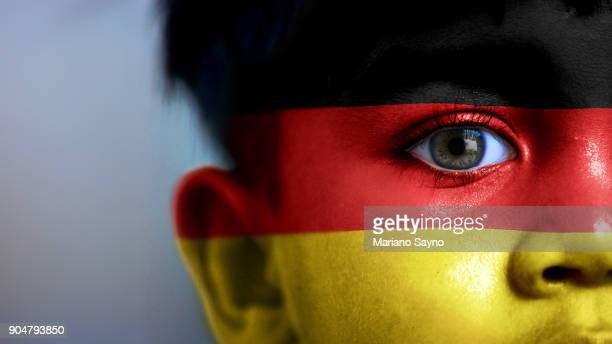 Boy's face, looking at camera, cropped view with digitally placed Germany flag on his face.
