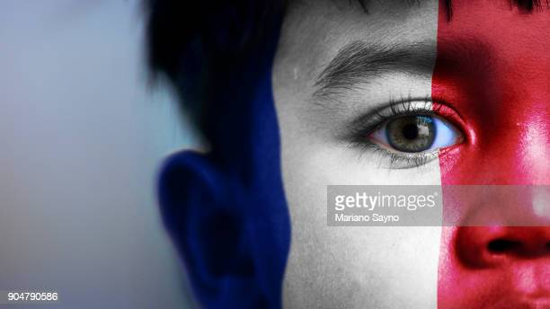 Boy's face, looking at camera, cropped view with digitally placed France flag on his face.