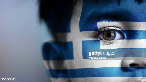 boy's face, looking at camera, cropped view with digitally placed greece flag on his face. - greek flag stock pictures, royalty-free photos & images