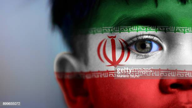 Boy's face, looking at camera, cropped view with digitally placed Iran flag on his face.