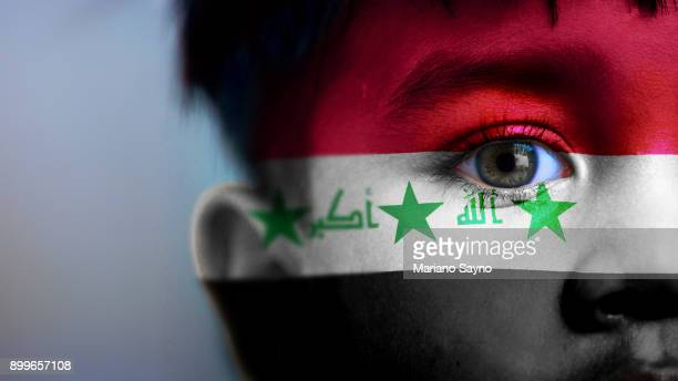 Boy's face, looking at camera, cropped view with digitally placed Iraq flag on his face.