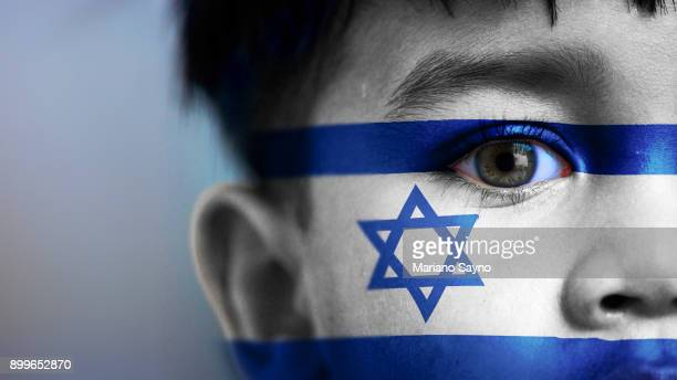 Boy's face, looking at camera, cropped view with digitally placed Israel flag on his face.