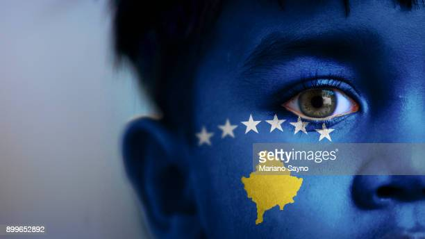 Boy's face, looking at camera, cropped view with digitally placed Kosovo flag on his face.