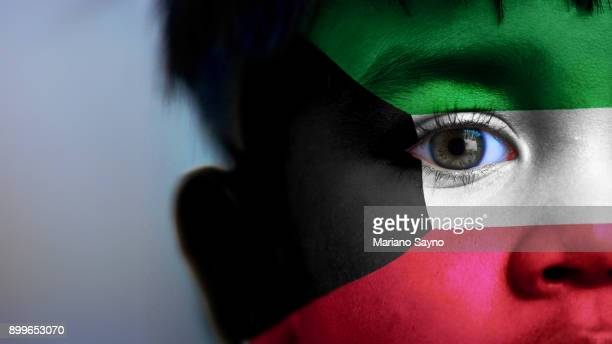 boy's face, looking at camera, cropped view with digitally placed kuwait flag on his face. - kuwaiti flag stock pictures, royalty-free photos & images