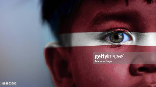 Boy's face, looking at camera, cropped view with digitally placed Latvia flag on his face.