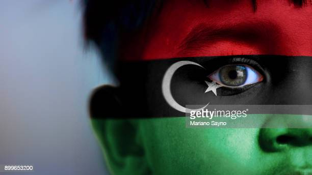 Boy's face, looking at camera, cropped view with digitally placed Libya flag on his face.
