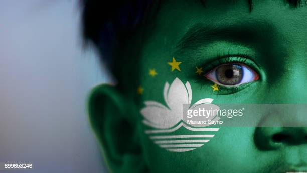 Boy's face, looking at camera, cropped view with digitally placed Macao flag on his face.
