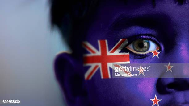boy's face, looking at camera, cropped view with digitally placed new zealand flag on his face. - new zealand flag stock photos and pictures