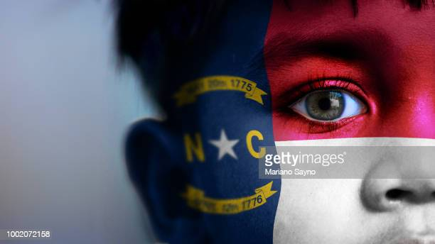 Boy's face, looking at camera, cropped view with digitally placed North Carolina State flag on his face.