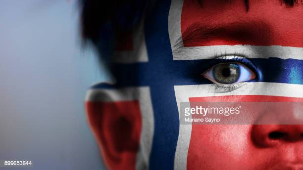 Boy's face, looking at camera, cropped view with digitally placed Norway flag on his face.