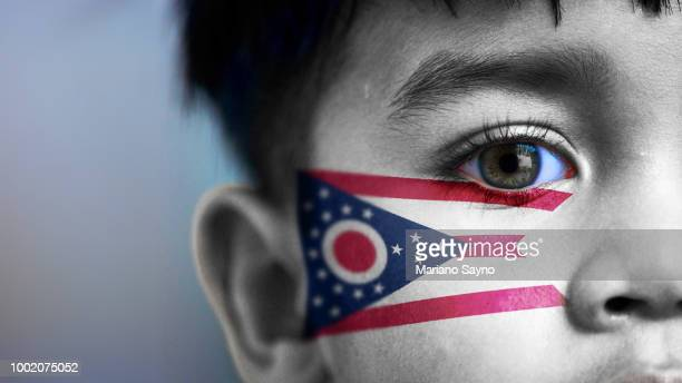 Boy's face, looking at camera, cropped view with digitally placed Ohio State flag on his face.