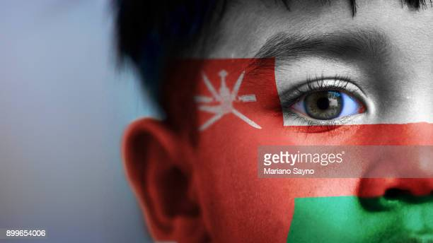 boy's face, looking at camera, cropped view with digitally placed oman flag on his face. - oman stock pictures, royalty-free photos & images