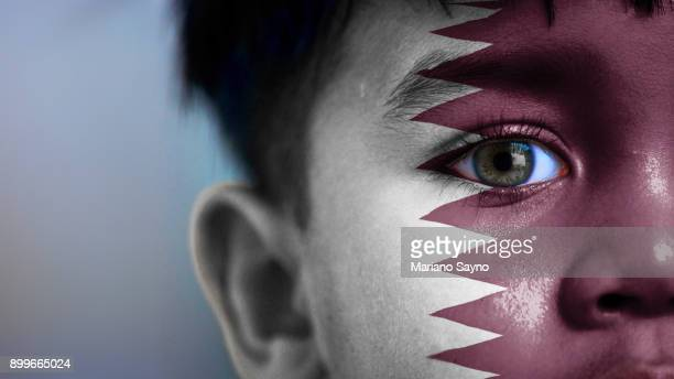 boy's face, looking at camera, cropped view with digitally placed qatar flag on his face. - qatar stock pictures, royalty-free photos & images