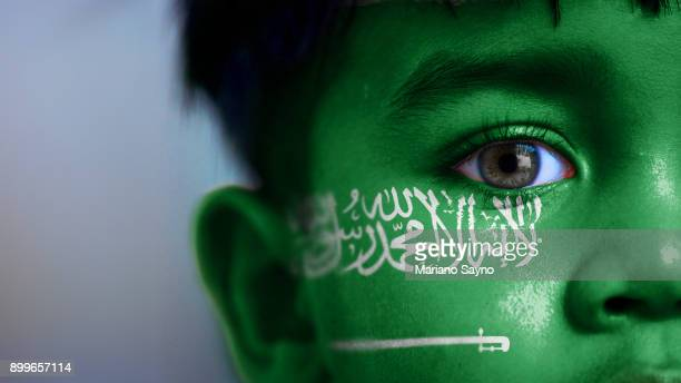 Boy's face, looking at camera, cropped view with digitally placed Saudi Arabia flag on his face.