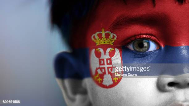 Boy's face, looking at camera, cropped view with digitally placed Serbia flag on his face.