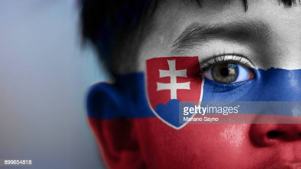 Boy's face, looking at camera, cropped view with digitally placed Slovak Republic flag on his face.