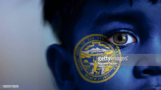 Boy's face, looking at camera, cropped view with digitally placed Nebraska State flag on his face.