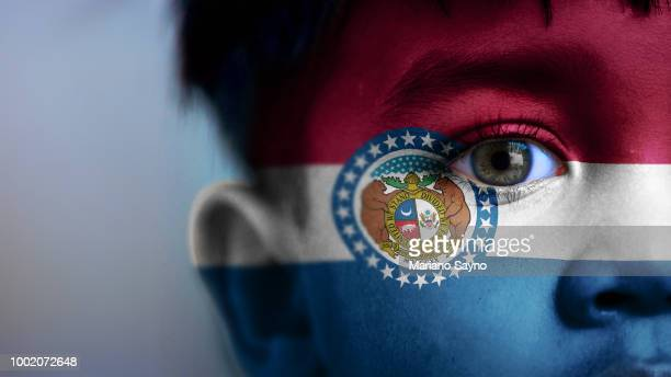 Boy's face, looking at camera, cropped view with digitally placed Missouri State flag on his face.