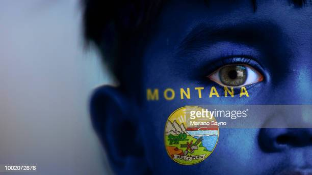 Boy's face, looking at camera, cropped view with digitally placed Montana State flag on his face.