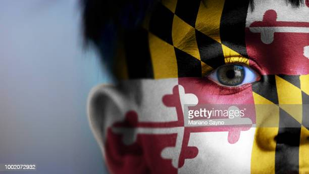 Boy's face, looking at camera, cropped view with digitally placed Maryland State flag on his face.