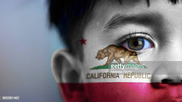 Boy's face, looking at camera, cropped view with digitally placed California State flag on his face.