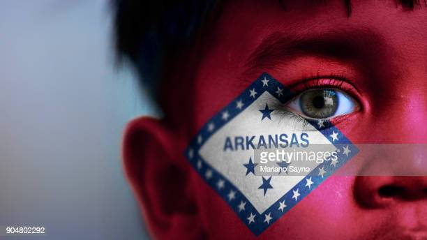 Boy's face, looking at camera, cropped view with digitally placed Arkansas State flag on his face.