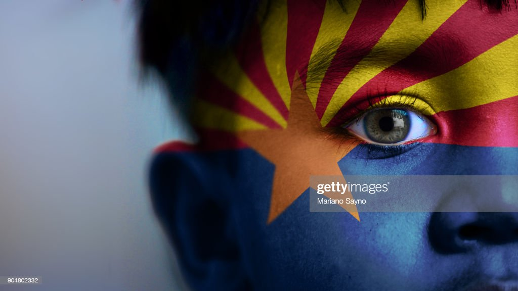 Boy's face, looking at camera, cropped view with digitally placed Arizona State flag on his face. : Stock Photo