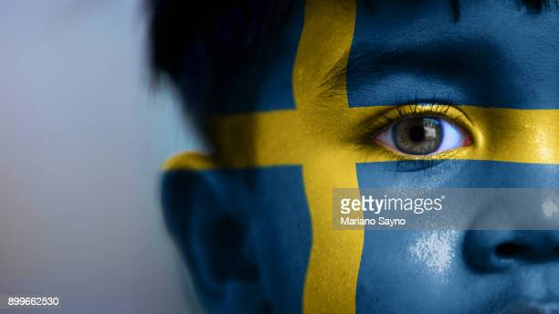 Boy's face, looking at camera, cropped view with digitally placed Sweden flag on his face.