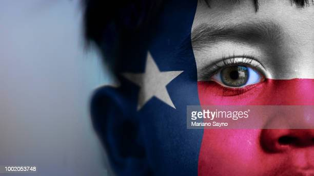Boy's face, looking at camera, cropped view with digitally placed Texas State flag on his face.