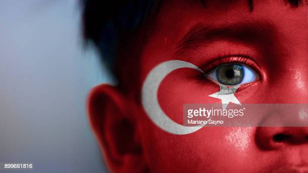 Boy's face, looking at camera, cropped view with digitally placed Turkey flag on his face.