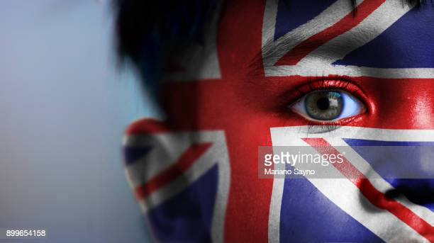 Boy's face, looking at camera, cropped view with digitally placed United Kingdom flag on his face.