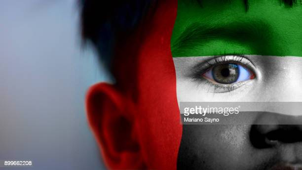 boy's face, looking at camera, cropped view with digitally placed united arab emirates flag on his face. - united arab emirates flag stock photos and pictures