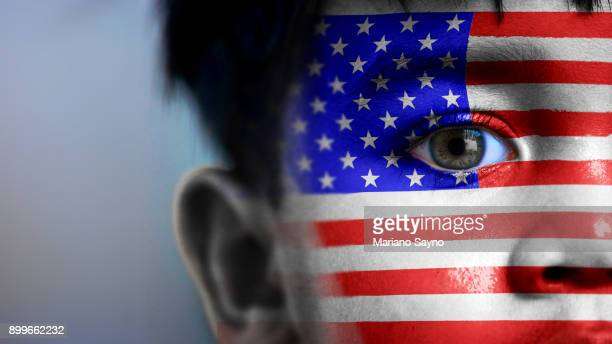 Boy's face, looking at camera, cropped view with digitally placed USA flag on his face.