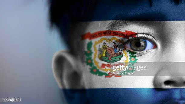 boy's face, looking at camera, cropped view with digitally placed west virginia  state flag on his face. - charleston west virginia stock pictures, royalty-free photos & images