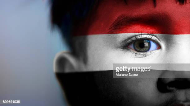 Boy's face, looking at camera, cropped view with digitally placed Yemen flag on his face.