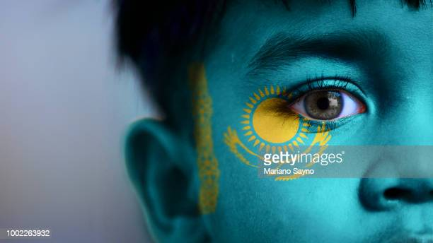 boy's face with digitally placed kazakhstan flag on his face. - kazakhstan stock pictures, royalty-free photos & images