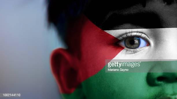 boy's face with digitally placed palestine flag on his face. - palestijnse gebieden stockfoto's en -beelden