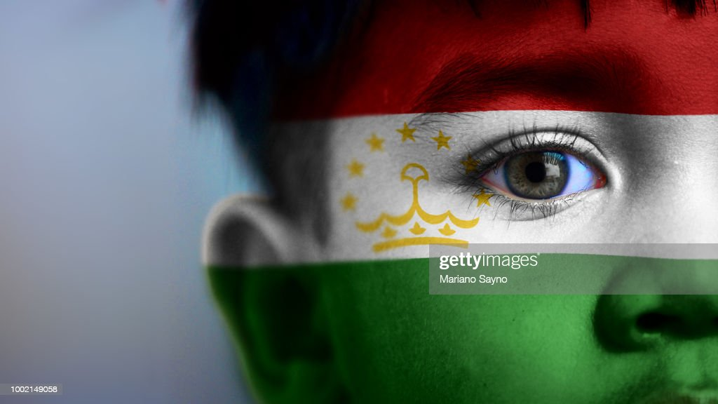 Boy's face with digitally placed Tajikistan flag on his face. : Stock Photo