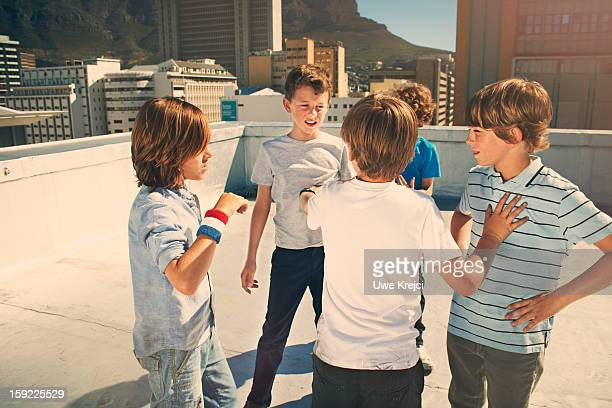 Boys (8 -10 years) fighting on roof top