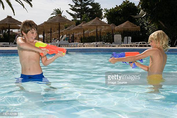 Boys fighting with water pistols