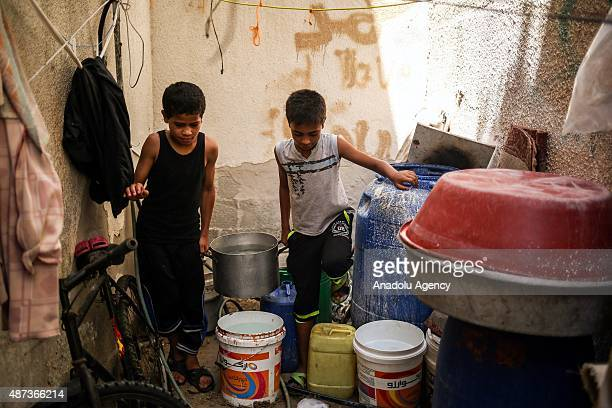 Boys fill buckets with water brought by a water truck in Gaza City, Gaza on September 9, 2015. At least 120,000 Palestinians face water crisis just...
