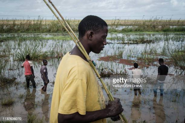 Boys fish in a flooded area after the passage of the cyclone Idai near Tica Mozambique on March 24 2019 Cyclone Idai smashed into Mozambique's coast...