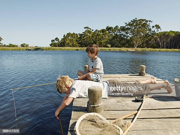 2 boys fishing at lakeside