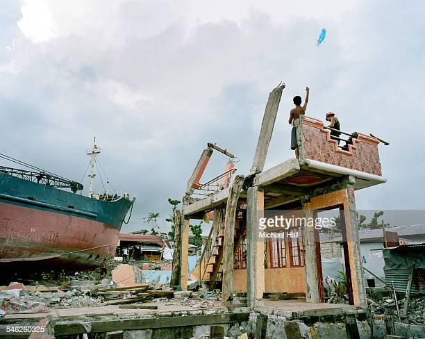 boys flying kite from remains of ravaged building - damaged stock pictures, royalty-free photos & images