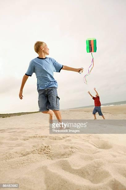 boys flying kite on beach - thinkstock foto e immagini stock